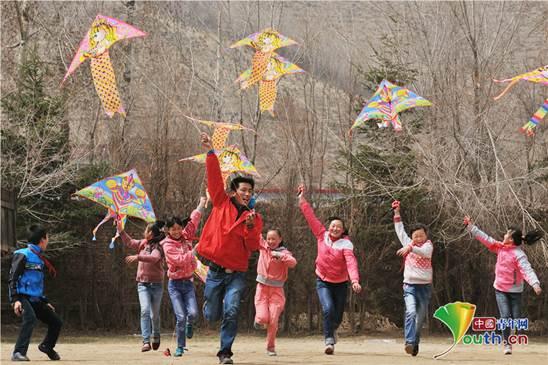 刘洋与支教学校的孩子们放风筝。本人供图