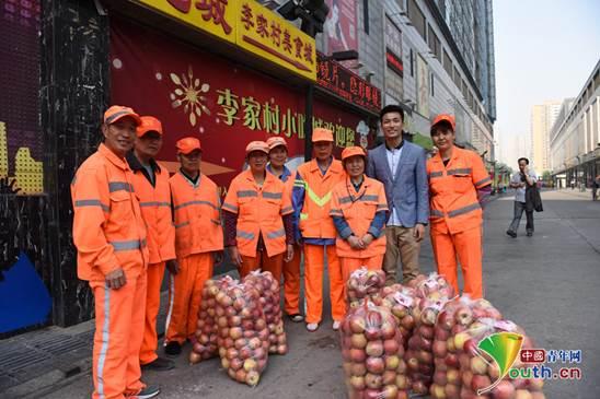 """刘洋带领""""爱心青年帮""""发起""""助爱贫困果农 慰问城市环卫工""""活动。本人供图"""