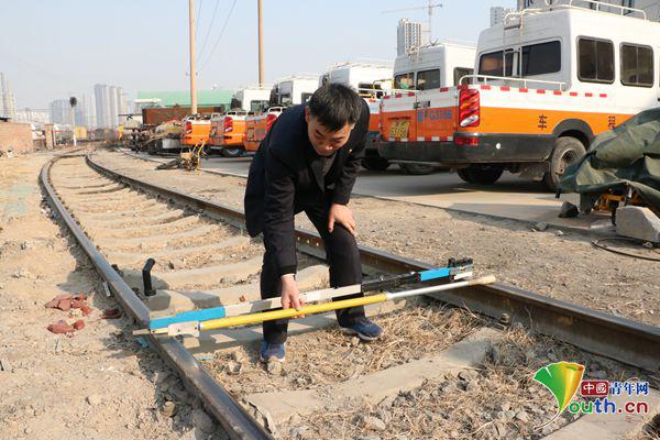 张立昌演示新式轨廓道尺与清淡道尺行使区别。中国青年网记者 李川 摄